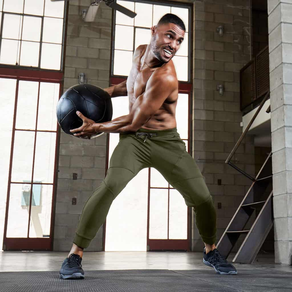 Hylete Flexion Workout Pants for Men in Heather Olive with medicine ball