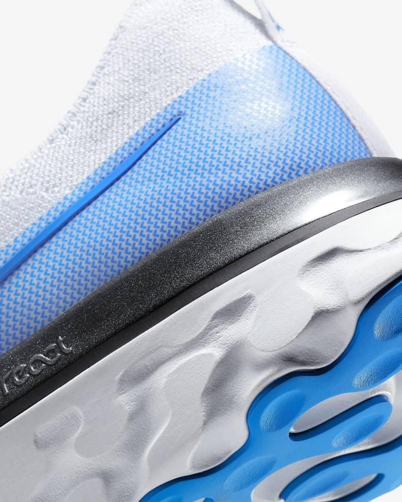 Heel closeup of the Nike React Infiinity Run Flyknit in True White/White/Pure Platinum/Photo Blue