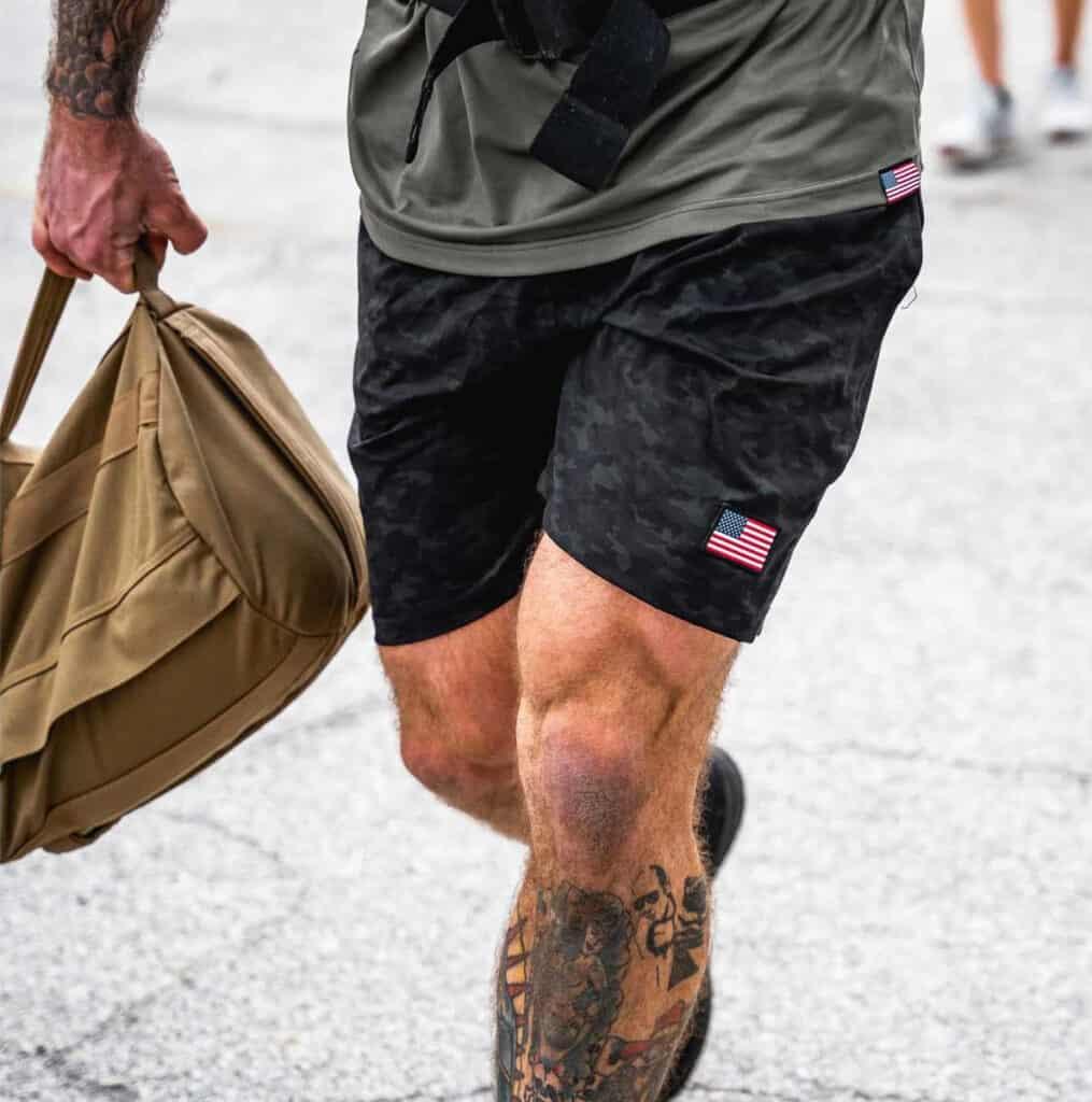 GORUCK Men's American Training Shorts dark camo walking with a ruckbag