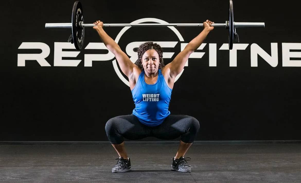 Rep Fitness Rep Black Bumper Plates with an athlete